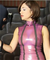 A latex wearing wife is caning her husband.