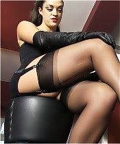 The stunning Hunteress, dressed in black lingerie, is worshiped by a strong slave.