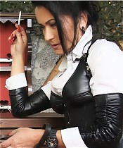 Arrogant Mistress in black leather and her human ashtray.